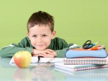 Мальчик за партой, перед ним пенал, тетарди и яблоко