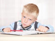 Раздраженный школьник сидит над тетрадями