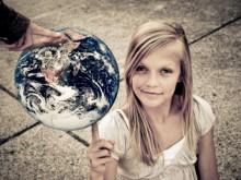 Девочка держит на пальце земной шар