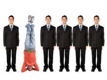 В ряду бизнесменов небрежно одетый парень стоит на голове