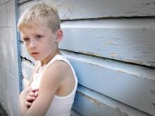 Мальчик стоит, опершись о стену, руки скрещены на груди
